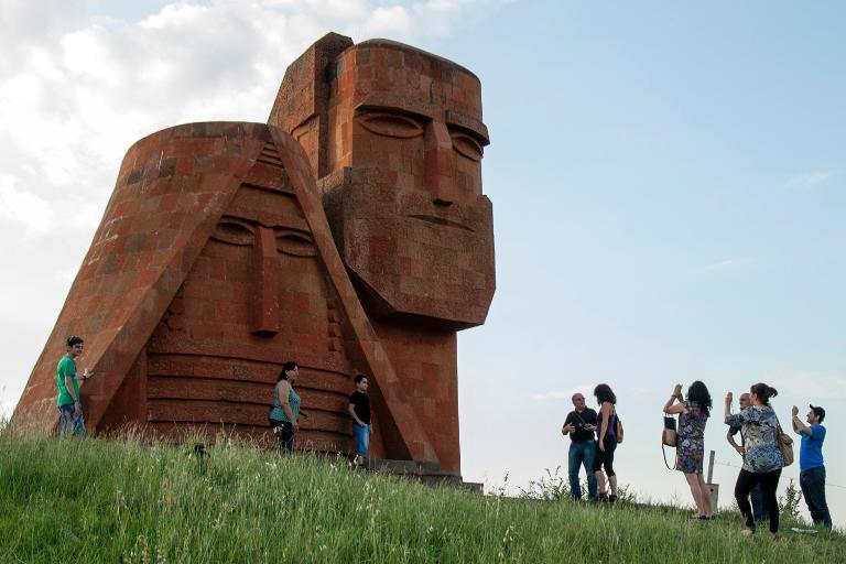 Tourists visit Grandmother and Granfather monument outside city of Stepanakert in Armenian-controlled Azerbaijani region of Nagorny Karabakh on June 26, 2013