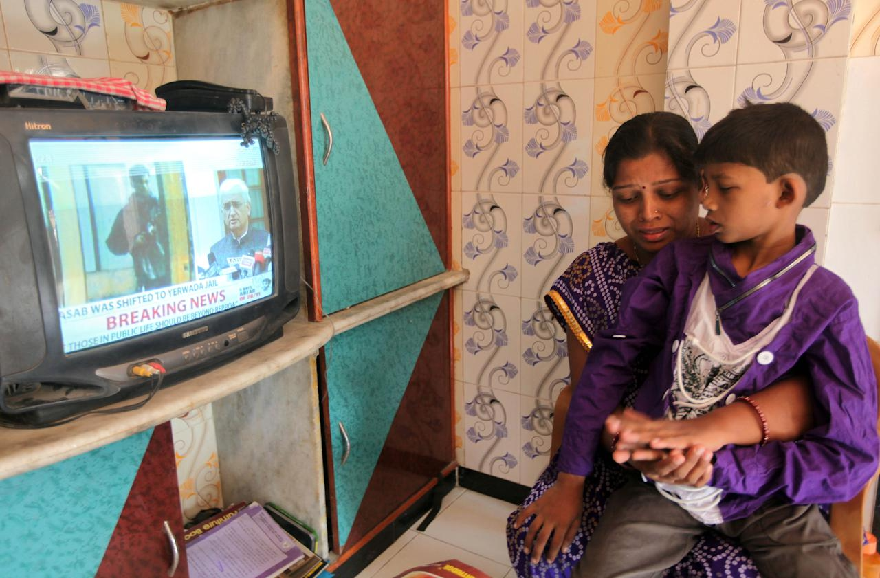 Karuna, wife of a victim of the 2008 Mumbai attacks Thakur Budha Vaghela, breaks down as she watches with her son Neeraj the news of Mohammed Ajmal Kasab's execution, in Mumbai, India, Wednesday, Nov. 21, 2012. India executed Kasab, the lone surviving gunman from the 2008 Mumbai terror attack early Wednesday, four years after Pakistani gunmen blazed through India's financial capital, killing 166 people and throwing relations between the nuclear-armed neighbors into a tailspin. (AP Photo/Rajanish Kakade)