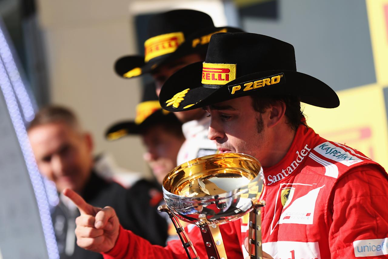 AUSTIN, TX - NOVEMBER 18:  Fernando Alonso of Spain and Ferrari celebrates on the podium after finishing third during the United States Formula One Grand Prix at the Circuit of the Americas on November 18, 2012 in Austin, Texas.  (Photo by Mark Thompson/Getty Images)