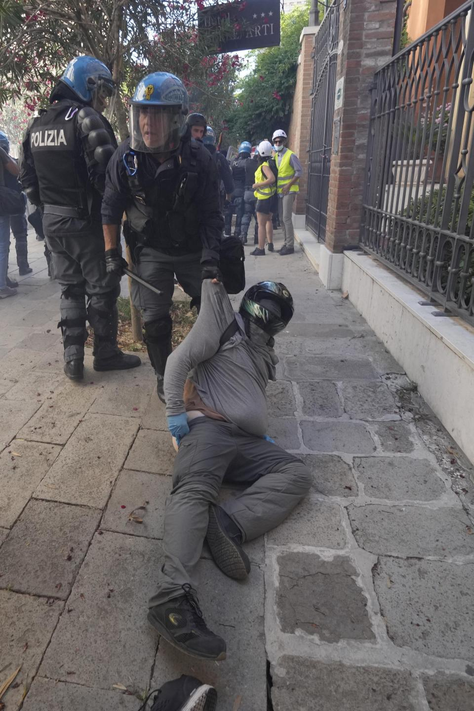 A demonstrator is blocked by an Italian policemen during clashes broke out between demonstrators and Italian Policemen in riot gears on the occasion of a protest against the G20 Economy and Finance ministers and Central bank governors' meeting in Venice, Italy, Saturday, July 10, 2021. (AP Photo/Luca Bruno)