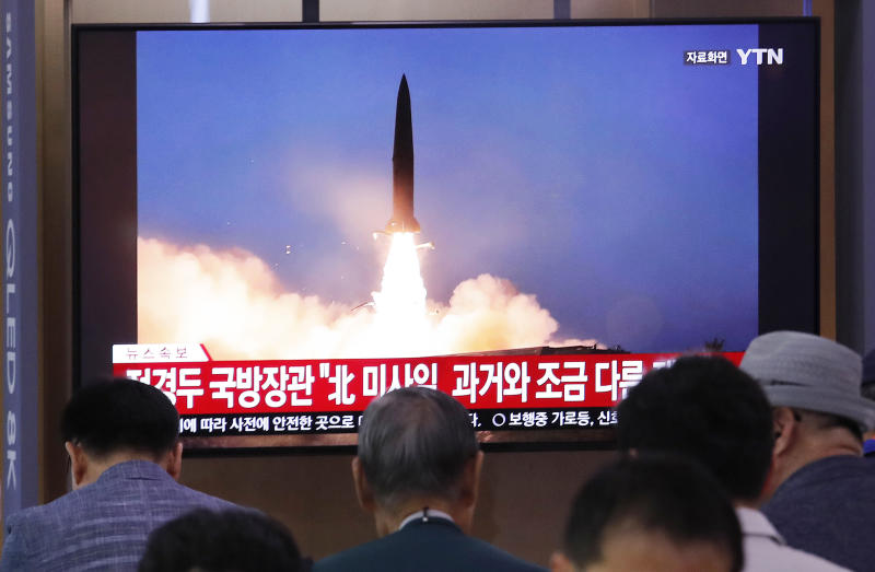 "People watch a TV showing a file image of North Korea's missile launch during a news program at the Seoul Railway Station in Seoul, South Korea, Wednesday, July 31, 2019. North Korea on Wednesday fired several unidentified projectiles off its east coast, South Korea's military said, less than a week after the North launched two short-range ballistic missiles into the sea in a defiance of U.N. resolutions. The signs read: ""North Korea's missile is a bit different from the past."" (AP Photo/Ahn Young-joon)"