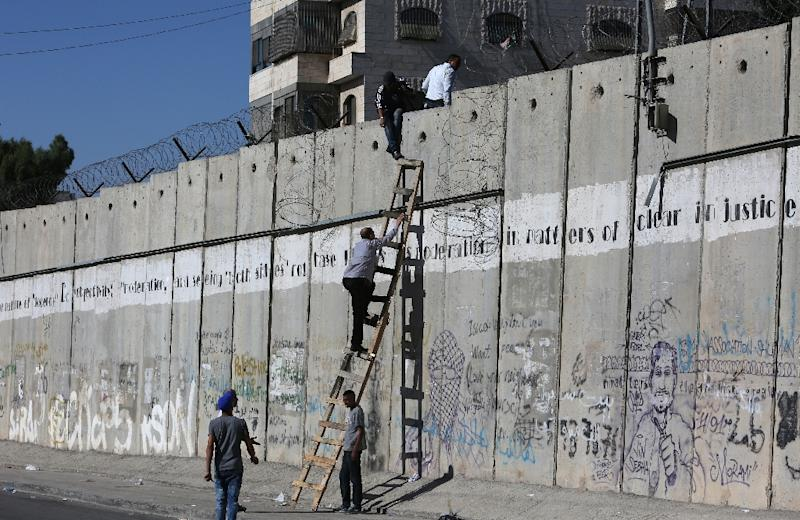 Palestinians climb over a section of Israel's separation barrier, near Qalandia checkpoint between Ramallah and Jerusalem, in July 2015 (AFP Photo/Abbas Momani)