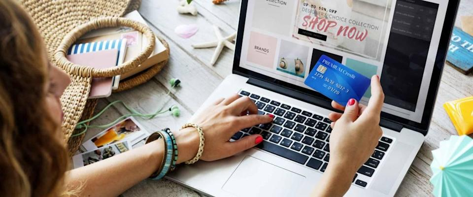 Woman shopping online with laptop open to site, credit card in her hand