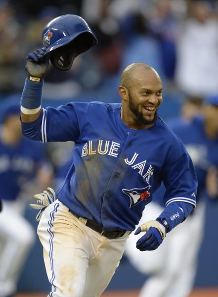 Toronto Blue Jays' Emilio Bonifacio celebrates after scoring the game-winning run off a hit by teamate Rajai Davis in the 18th inning of a baseball game against the Texas Rangers in Toronto, on Saturday, June 8, 2013. The Blue Jays on 4-3 in 18 innings. (AP Photo/The Canadian Press, J.P. Moczulski)