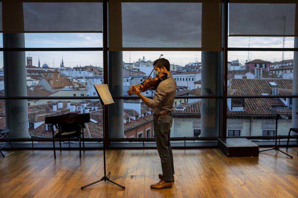 A musician in a face mask plays the violin at a rehearsal at the Teatro Real in Madrid, Spain, Friday, Nov. 13, 2020. The theater is one of the few major opera houses that have reopened during the pandemic, although to smaller audiences. (AP Photo/Bernat Armangue)
