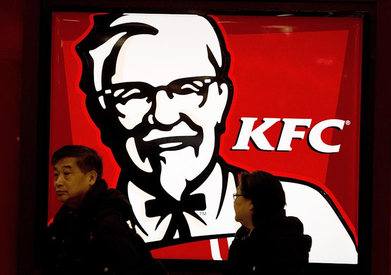 A Chinese couple walk past a KFC restaurant at a shopping mall in Beijing Monday, Feb. 25, 2013. KFC launched a campaign Monday to rebuild its battered brand in China, promising tighter quality control after a scandal over misuse of drugs by its poultry suppliers. (AP Photo/Andy Wong)