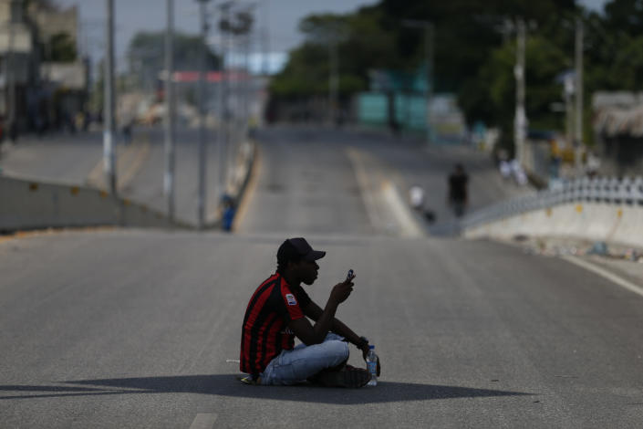A man using his cell phone sits in the shade of a street sign in the middle of a normally busy main road that was devoid of drivers, as protesters calling for the resignation of President Jovenel Moïse gathered at a bridge in the Delmar area of Port-au-Prince, Haiti, Thursday, Oct. 17, 2019. Haiti's embattled president was forced on Thursday to hold a private ceremony amid heavy security for what is usually a public celebration of one of the country's founding fathers, revolution leader Jean-Jacques Dessalines. (AP Photo/Rebecca Blackwell)