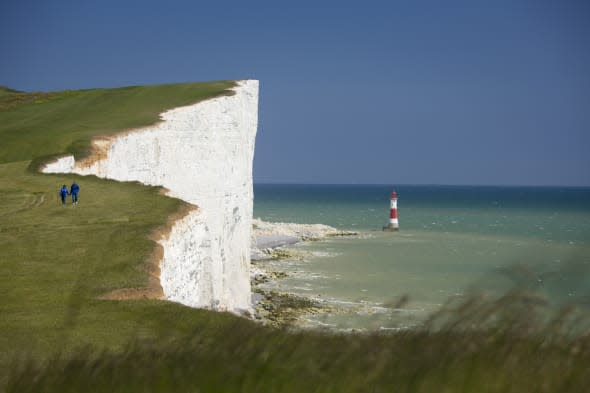 A couple walking along the clifftop of the dramatic coastline at Beachy Head., Beachy Head, East Sussex, England. Additional Cre