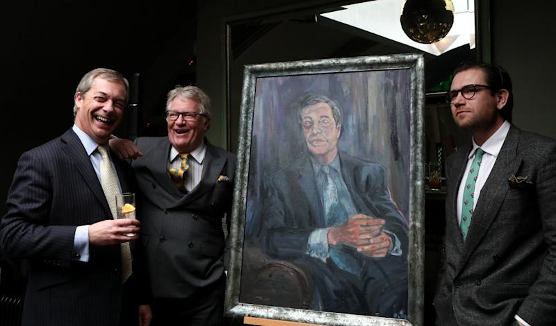 (left to right) Nigel Farage, comedian Jim Davidson and artist Dan Llywelyn Hall, stand beside a portrait titled Mr Brexit, at L'Escargot Restaurant in London.