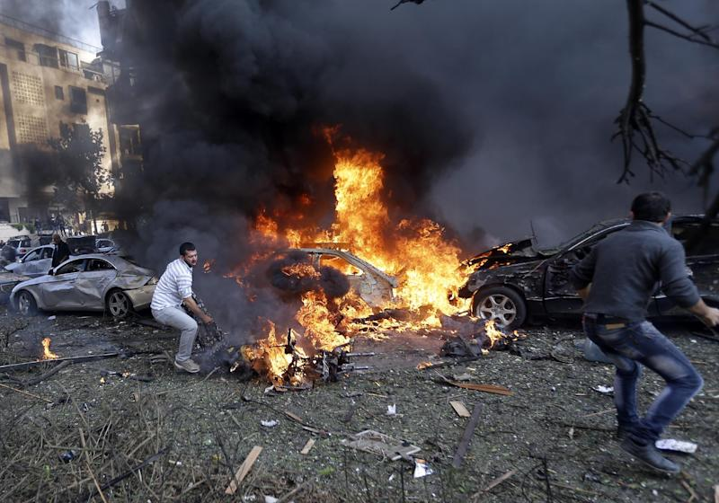 Lebanese men run to remove dead bodies from burned cars, at the scene where two explosions have struck near the Iranian Embassy killing several, in Beirut, Lebanon, Tuesday Nov. 19, 2013. The blasts in south Beirut's neighborhood of Janah also caused extensive damage on the nearby buildings and the Iranian mission. The area is a stronghold of the militant Hezbollah group, which is a main ally of Syrian President Bashar Assad in the civil war next door. It's not clear if the blasts are related to Syria's civil war. (AP Photo/Hussein Malla)