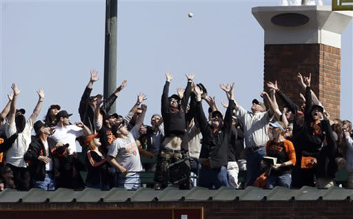 Fans reach for a home run ball hit by San Francisco Giants' Brandon Crawford off of Arizona Diamondbacks pitcher David Hernandez during the ninth inning of a baseball game in San Francisco, Wednesday, April 24, 2013. (AP Photo/Jeff Chiu)