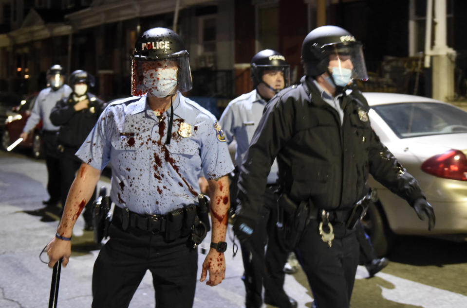 A Philadelphia police officer is covered with an unidentified red substance during a confrontation with protesters, Tuesday, Oct. 27, 2020, in Philadelphia. Hundreds of demonstrators marched in West Philadelphia over the death of Walter Wallace Jr., a Black man who was killed by police in Philadelphia on Monday. (AP Photo/Michael Perez)
