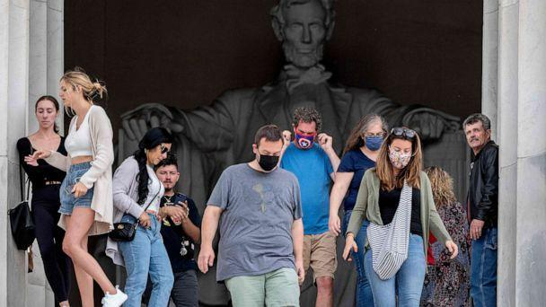 PHOTO: Tourists, some in face masks while others are not, visit the Lincoln Memorial in Washington, D.C., May 14, 2021.  (Jim Watson/AFP via Getty Images)