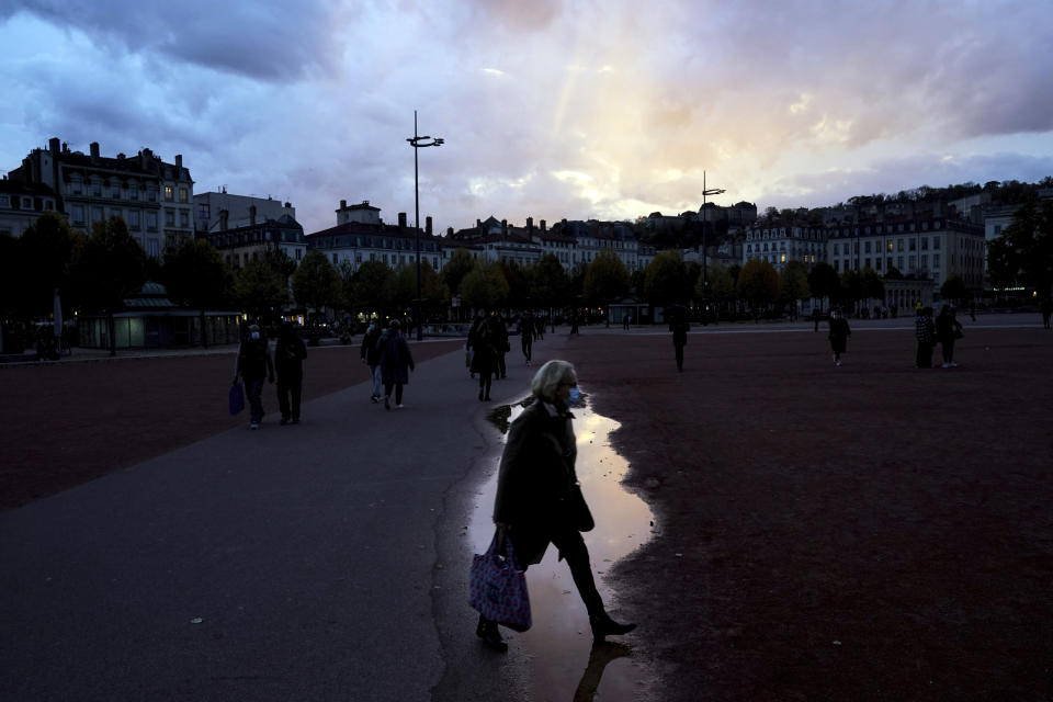 A woman wearing a mask walks in the street in the center of Lyon, central France, Wednesday, Oct. 28, 2020. France is bracing for a potential new lockdown as the president prepares a televised address Wednesday aimed at stopping a fast-rising tide of virus patients filling French hospitals and a growing daily death toll. French markets opened lower on expectations that President Emmanuel Macron will announce some kind of lockdown Wednesday. (AP Photo/Laurent Cipriani)
