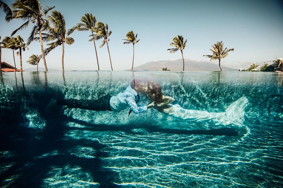 <p>A newlywed couple is shown kissing underwater in Maui. (Photo: Junebug Weddings/Caters News) </p>