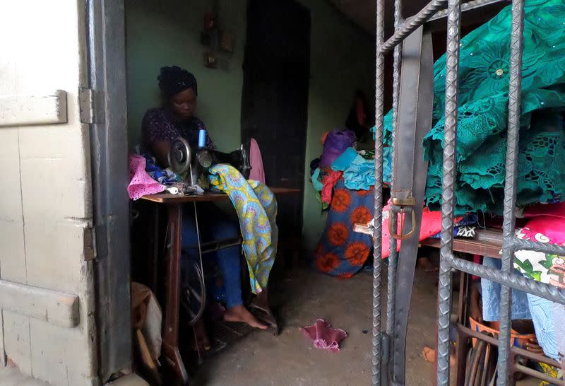 Kemi Adepoju, a dressmaker, sews a dress with a sewing machine in her shop amid the spread of the coronavirus disease (COVID-19) in Lagos