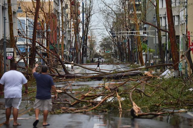 <p>Men walk damaged trees after the passage of Hurricane Maria, in San Juan, Puerto Rico, on Sept. 20, 2017. (Photo: Hector RetamalAFP/Getty Images) </p>