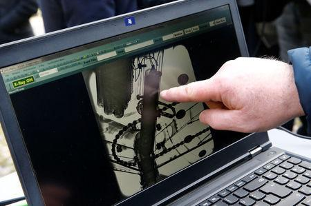 A staff show the detection of an engine in the frame of a bike during the demonstration of the use of the x-ray machine after an International Cycling Union (UCI) news conference on the fight against technological fraud in Geneva, Switzerland March 21, 2018. REUTERS/Denis Balibouse