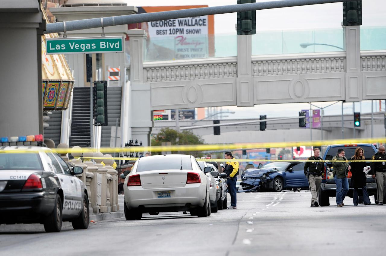 LAS VEGAS, NV - FEBRUARY 21:  Las Vegas Metropolitan Police Department officers investigate the site of what is being described as a gun battle between shooters in vehicles along the Las Vegas Strip on February 21, 2013 in Las Vegas, Nevada. According to reports gunshots were fired between a black SUV and a Maserati, causing the Maserati to crash into a taxi that burst into flames. Five vehicles were involved in the subsequent crash with the Maserati driver and two people in the taxi being killed.  (Photo by David Becker/Getty Images)