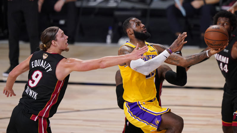 Los Angeles Lakers' LeBron James, right, drives to the basket past Miami Heat's Kelly Olynyk (9) during the second half of Game 1 of basketball's NBA Finals Wednesday, Sept. 30, 2020, in Lake Buena Vista, Fla. (AP Photo/Mark J. Terrill)