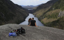 Sidney Gleason, left, and Joe Gorsuch, both of Syracuse, kiss while taking in the view of Lower Ausable Lake at Indian Head summit inside the Adirondack Mountain Reserve, Saturday, May 15, 2021, near St. Huberts, N.Y. A free reservation system went online recently to control the growing number of visitors packing the parking lot and tramping on the trails through the private land of the Adirondack Mountain Reserve. The increasingly common requirements, in effect from Maui to Maine, offer a trade-off to visitors, sacrificing spontaneity and ease of access for benefits like guaranteed parking spots and more elbow room in the woods. (AP Photo/Julie Jacobson)