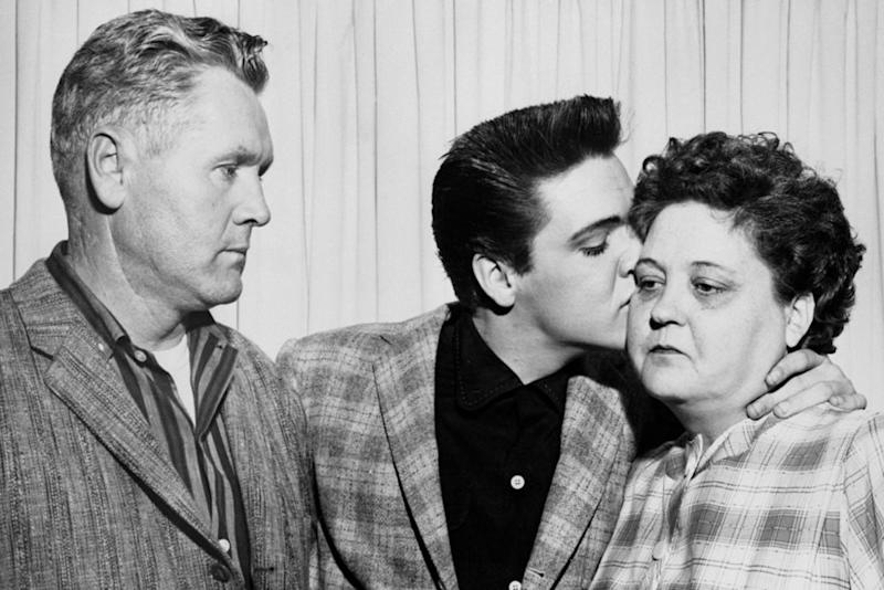 Elvis Presley with mother, Gladys, and father, Vernon, at his induction into the U.S. Army | Bettmann/Getty