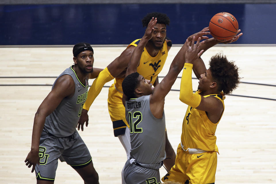 West Virginia guard Miles McBride (4) shoots while defended by Baylor guard Jared Butler (12) and West Virginia forward Derek Culver (1) and Baylor forward Flo Thamba (0) look on during the first half of an NCAA college basketball game Tuesday, March 2, 2021, in Morgantown, W.Va. (AP Photo/Kathleen Batten)