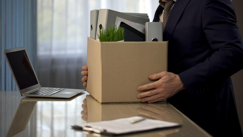 Employee putting his stuff from work desk in carton box, leaving job, retirement