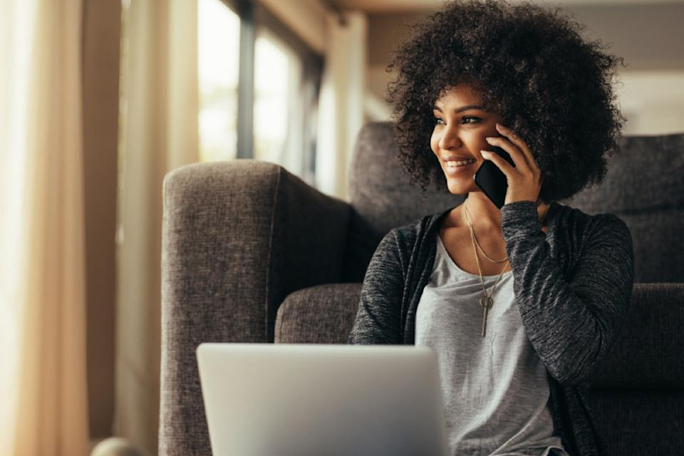 black woman smiling while on the phone in front of her laptop