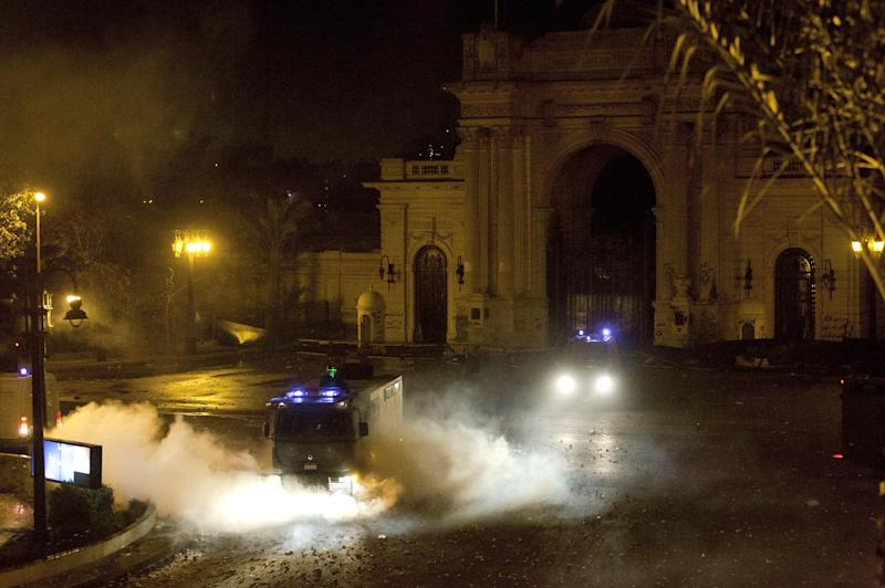 Egyptian riot police vehicles secure the entrance of the Qasr al-Kobba palace, one of the president's secondary residences amid tear gas during clashes with protesters following an-anti president Mohammed Morsi protest, in Cairo, Egypt, Friday, Feb. 15, 2013. Several thousand hard-line Islamists rallied in Cairo on Friday against a recent wave of violent anti-government protests, while liberal activists staged a smaller demonstration across town to call for accountability and justice from the country's leaders. (AP Photo/Nasser Nasser)