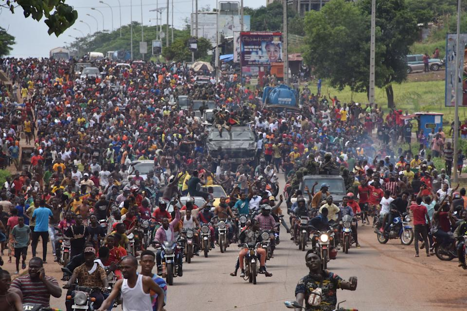 Seen here, People celebrate in the streets with members of Guinea's armed forces after the arrest of the country's president.