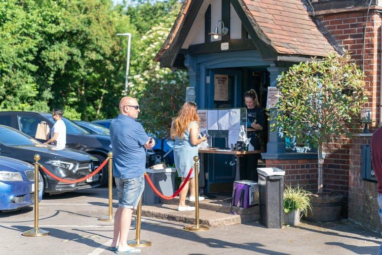 People queuing outside a pub.