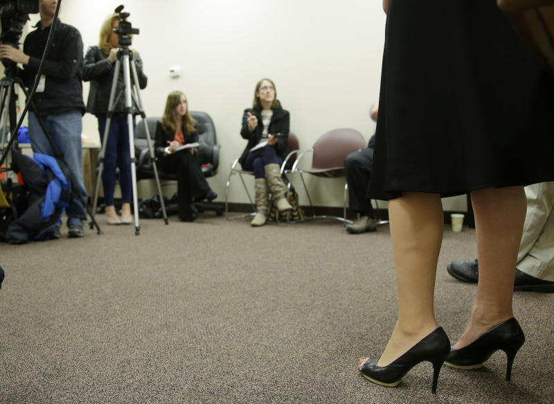 """Heather Abbott of Newport, RI., wears her new """"high-definition"""" prosthetic leg, left, which now allows her to also wear high heels and skirts as she talks with reporters during a media availability in Warwick, RI., Thursday, Nov. 7, 2013. Abbott lost her left leg in the April 15, 2013 Boston Marathon bombings. (AP Photo/Stephan Savoia)"""