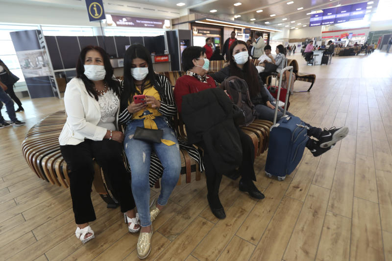 People wearing face masks wearing masks wait for the arrival of their relatives at the Mariscal Sucre International Airport, in Quito, Ecuador, Saturday, Feb. 29, 2020. Officials in Ecuador on Saturday confirmed the first case of the new coronavirus in the South American nation. (AP Photo/Dolores Ochoa)