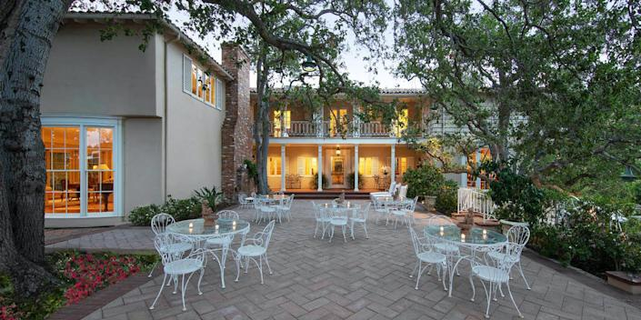 an outdoor space behind the lit home full of garden chairs and tables