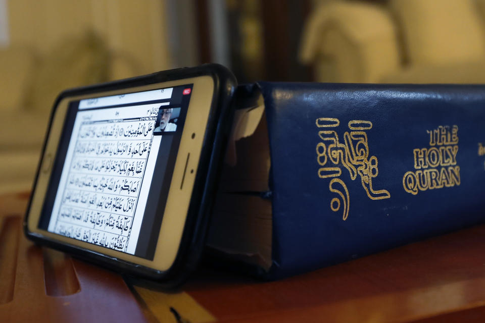 In this Tuesday, April 28, 2020, photo, Asghar Ali Khan's mobile phone rests against the Quran as he watches a virtual Quran study with other men during Ramadan at his Wheeling, Ill., home. (AP Photo/Charles Rex Arbogast)