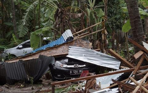 Cars are covered by debris at an area ravaged by a tsunami in Carita, Indonesia - Credit: AP