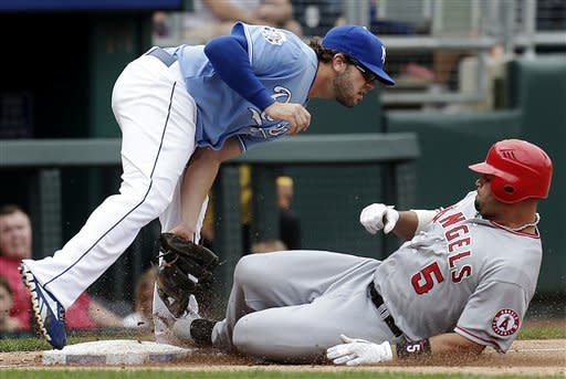 Los Angeles Angels' Albert Pujols, right, is forced out at third by Kansas City Royals third baseman Mike Moustakas while trying to stretch a double during the fifth inning of a baseball game, Sunday, Sept. 16, 2012, in Kansas City, Mo. (AP Photo/Charlie Riedel)