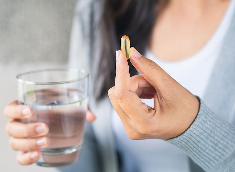 Woman holding fish oil vitamin pill supplement alongside a glass of water