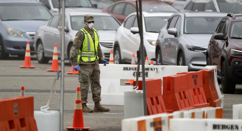 """FILE - In this Friday, March 20, 2020 file photo, a member of the New Jersey National Guard helps direct traffic at COVID-19 drive-through testing center in Paramus, N.J. On Friday, March 20, 2020, The Associated Press reported on stories circulating online incorrectly asserting that within 48-72 hours the president will evoke what is called the Stafford Act, will order a two week mandatory quarantine for the nation, and that the National Guard will mobilize and martial law will go into effect. The National Security Council knocked down the rumors on Twitter. """"As we saw over the wkend, disinfo is being spread online about a supposed national lockdown and grounding flights. Be skeptical of rumors. Make sure you're getting info from legitimate sources,"""" the council tweeted. (AP Photo/Seth Wenig)"""