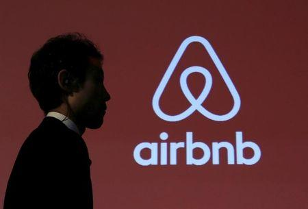 FILE PHOTO -  A man walks past a logo of Airbnb after a news conference in Tokyo