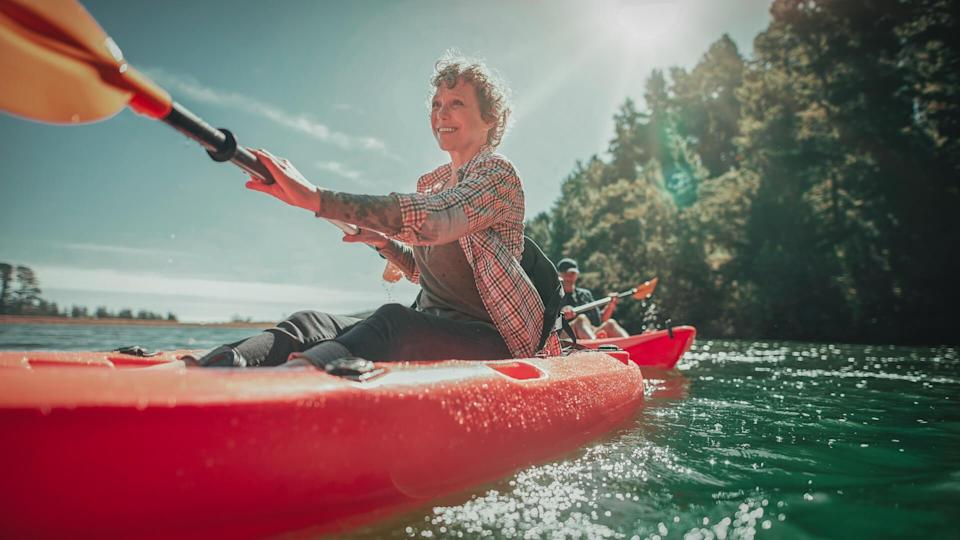 Shot of senior woman canoeing in lake on a summer day.
