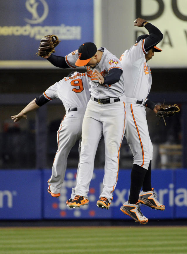 Baltimore Orioles' David Lough, left, Nick Markakis and Adam Jones, right, celebrate after the Orioles defeated the New York Yankees 5-4 in a baseball game Wednesday, April 9, 2014, at Yankee Stadium in New York. (AP Photo/Bill Kostroun)