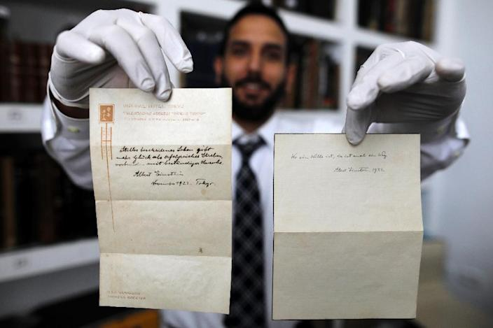 Gal Winner, owner and manager of the Winner's auction house in Jerusalem, on October 19, 2017 displays two notes written by Albert Einstein in 1922 on hotel stationary from the Imperial Hotel in Tokyo, Japan (AFP Photo/MENAHEM KAHANA)