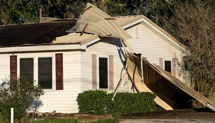 A metal roof is peeled off of a house in New Iberia, Louisiana, on Saturday morning. Oct. 10, 2020