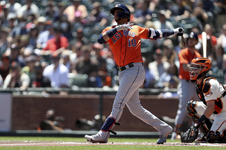 Houston Astros' Yuli Gurriel, left, hits a 2-run home run in front of San Francisco Giants' Buster Posey, right, during the first inning of a baseball game in San Francisco, Sunday, Aug. 1, 2021. (AP Photo/Jed Jacobsohn)