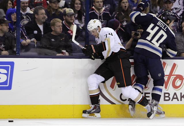 Anaheim Ducks' Peter Holland, left, checks Columbus Blue Jackets' Jared Boll off of the puck during the second period of an NHL hockey game Sunday, Oct. 27, 2013, in Columbus, Ohio. The Ducks beat the Blue Jackets 4-3. (AP Photo/Jay LaPrete)