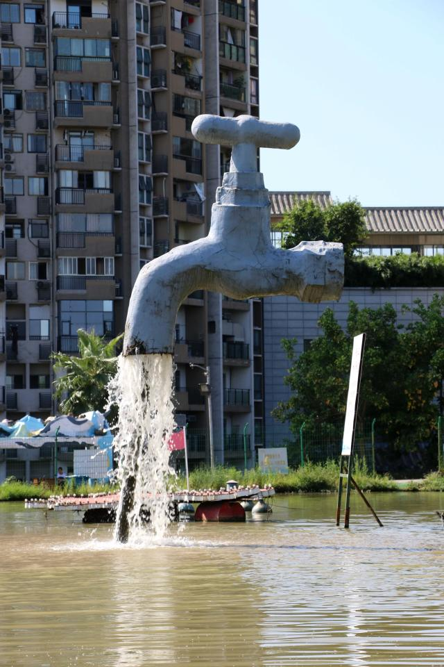 <p>A giant faucet statue dangling in the air runs water at a pond on September 3, 2018 in Chongqing, China. A giant faucet statue with water covering its inlet pipe dangles in the air in Chongqing on Monday. (Photo by VCG/VCG via Getty Images) </p>