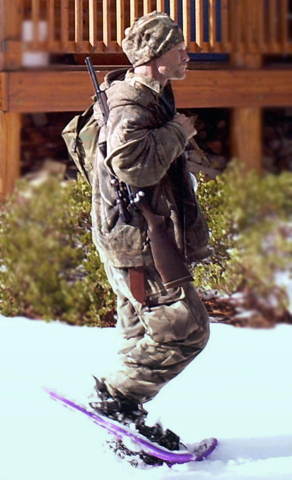 FILE - In this undated file photo provided by the Iron County Sheriff's Office in January 2013, a man identified as Troy James Knapp walks past a cabin in the remote southern Utah wildness near Zion National Park. Authorities say they have arrested Knapp, a survivalist suspected of burglarizing Utah cabins and evading law enforcement for years. (AP Photo/Iron County Sheriff, File)
