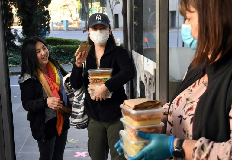 Michelle Cassell (R), student welfare officer at the Melbourne City Institute of Education, hands out free meals to international students cooked at the institute's kitchen